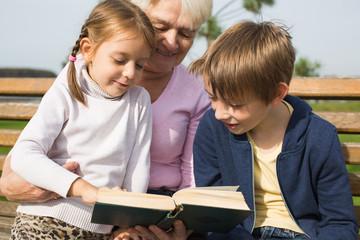 grgrandmother reading book to grandchildren outdoors