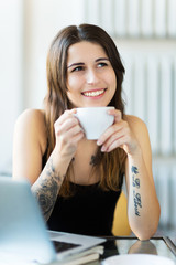 Tattooed woman enjoying a cup of coffee