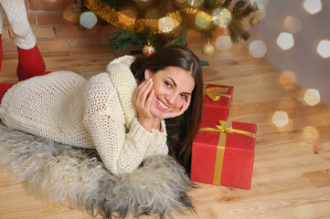beautiful smiling young woman with presents near Christmas tree