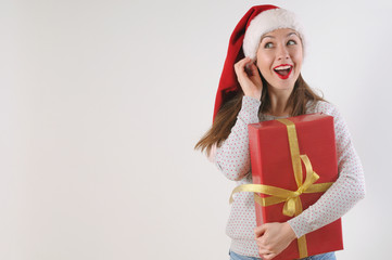 cute exciting young woman with present box in santa hat on white
