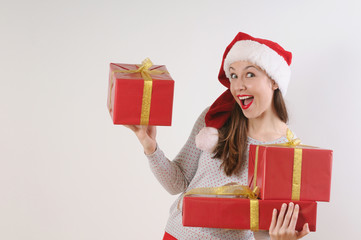 cute exciting young woman with present boxes in santa hat on whi