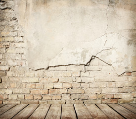 Cracked brick wall with wooden floor