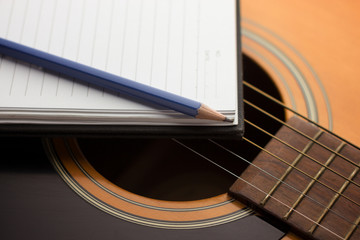 Notebook and pencil on guitar,Writing music