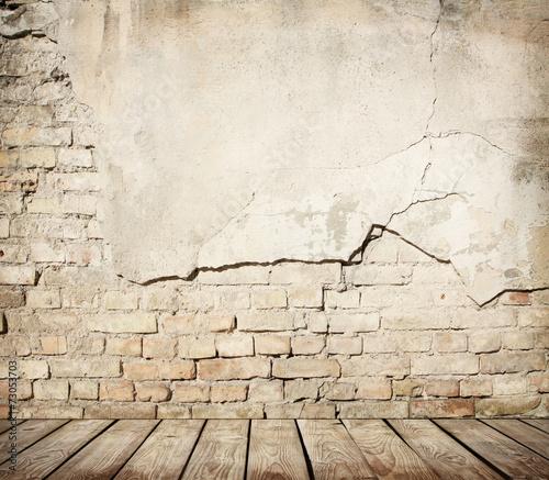 fototapeta na ścianę Pęknięty mur z drewnianą podłogą