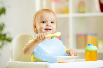 funny baby child boy eating itself with spoon in kitchen