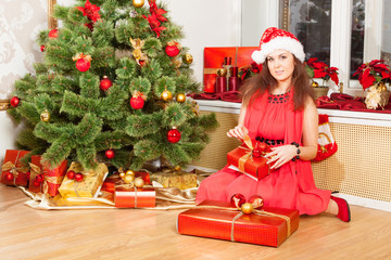 girl wearing red dress and xmas hat sits near New-Year's tree
