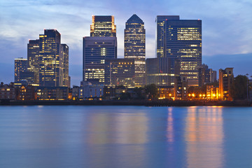 London business district skyline over Thames river at twilight