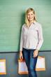 Frau steht vor Tafel in Schule