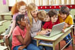 Kinder am Laptop mit Lehrer in Schule