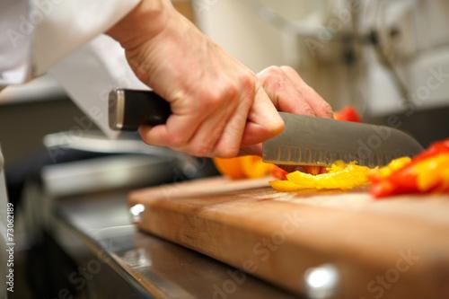 closeup on hands cutting yellow pepper