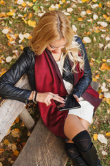 Beautiful blonde holding a digital tablet at park