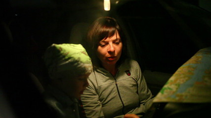 woman with her son on the road looking for a map at night 3