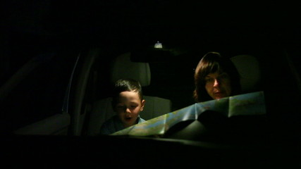 woman with her son on the road looking for a map at night