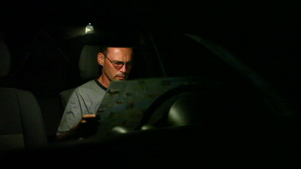 man looking at the road map at night
