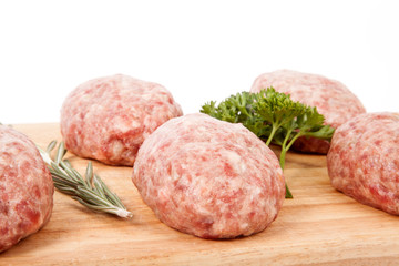 fresh uncooked patties on a wooden board with rosemary and parsl