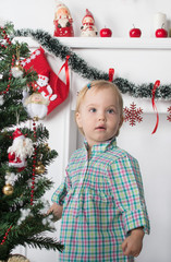 Cute surprised little girl stands near  the Christmas tree