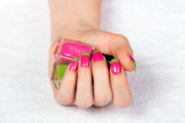 Female hand with manicure holds a two-color nail polish