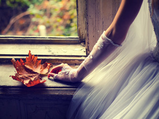 Detail of the brides hand holding autumn leaf while sitting in f