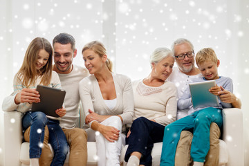 smiling family with tablet pc computers at home