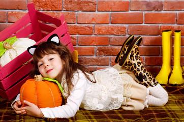 baby lying on the floor, hugging a pumpkin
