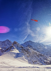 Red helicopter in the sky at swiss alps near Jungfrau mountain