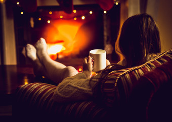 Toned photo of woman warming up with hot tea at fireplace