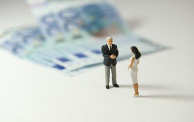 Un homme et une femme discutant devant des billets de 20€