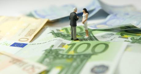 Homme et femme sur un tapis de billet en euros