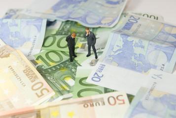 Hommes discutant sur un tapis de billet en euros