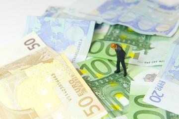 Homme seul au milieu de plusieurs billets en euros