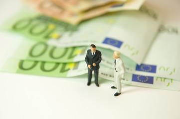 2 hommes discutant à coté d'un tas de billets en euros