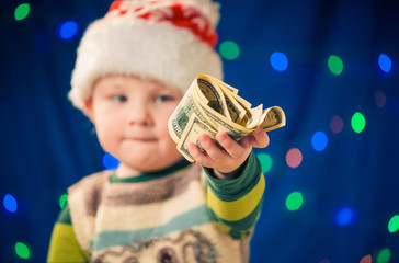 little boy give dollars at holiday lights background