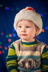 boy in christmas hat at colorful lights background
