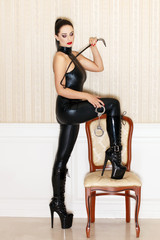 Sexy woman in latex catsuit with whip
