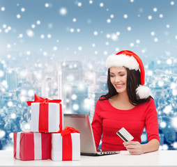 smiling woman with gifts, laptop and credit card