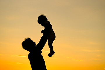 father holding and raising his son silhouette