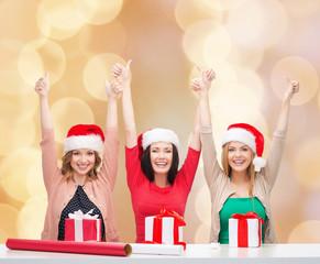 smiling women in santa helper hats packing gifts