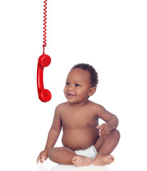 Adorable african baby looking a red telephone hunging