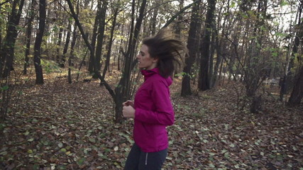 Beautiful woman jogging in autumn forest, super slow motion