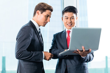 Two Business men with laptop and city skyline