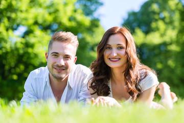 Paar im Glück liegt in Sonne auf Park Wiese