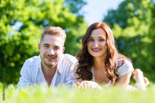canvas print picture Paar im Glück liegt in Sonne auf Park Wiese