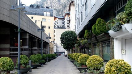 Clear street in Andorra-la-Vella with buildings and bushes.