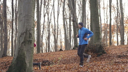 Couple jogging in autumn forest, super slow motion