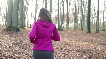 Young woman jogging in autumn forest, super slow motion