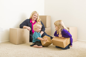Young Family In Empty Room with Moving Boxes