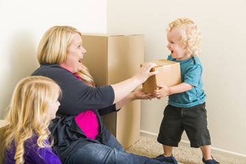 Young Family In Empty Room Playing With Moving Boxes