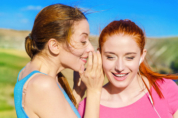 girl whispering into woman ear telling something latest gossip