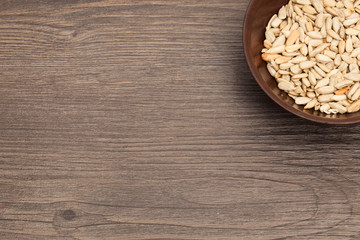 A white ceramic bowl full of Seeds over old wood background
