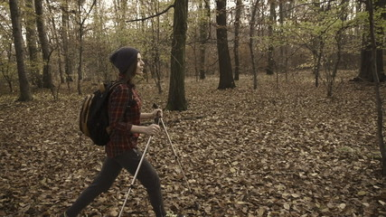Young woman trekking in autumn forest, super slow motion, 240fps